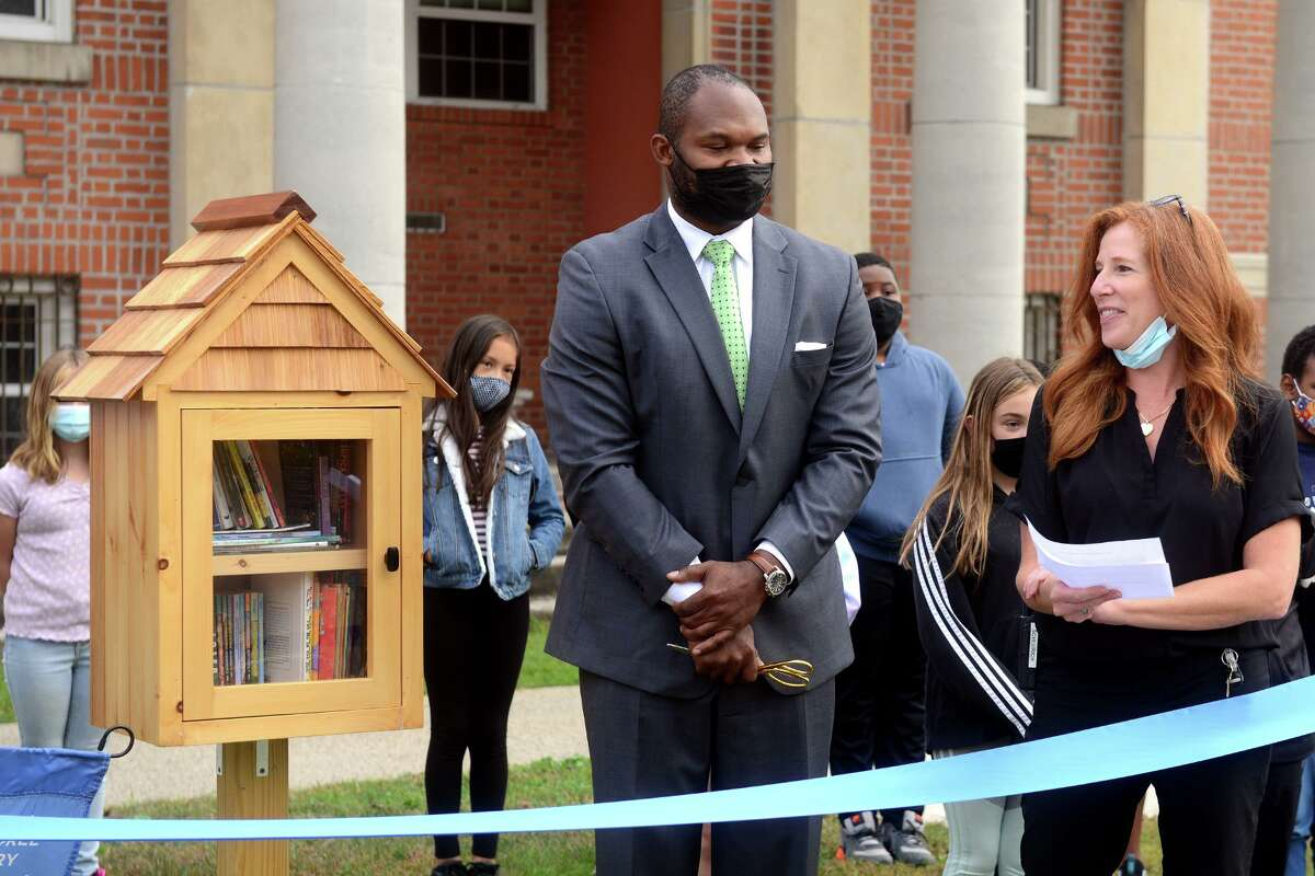 Reading consultant Kelly Scheurich, right, stands with Superintendent of School s Uyi Osunde as she speaks during a ribbon cutting ceremony for the new Little Free Library book sharing kiosk in front of Nichols Elementary School, in Stratford, Conn. Oct. 5, 2021.