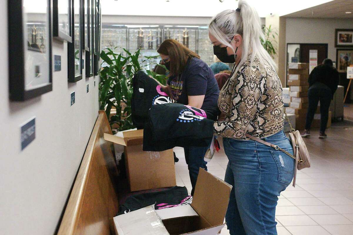 Matthys Elementary School staff member Rebecca Flores, front, and Diana Becerra from Sullivan Middle School, check their schools' T-shirt orders.