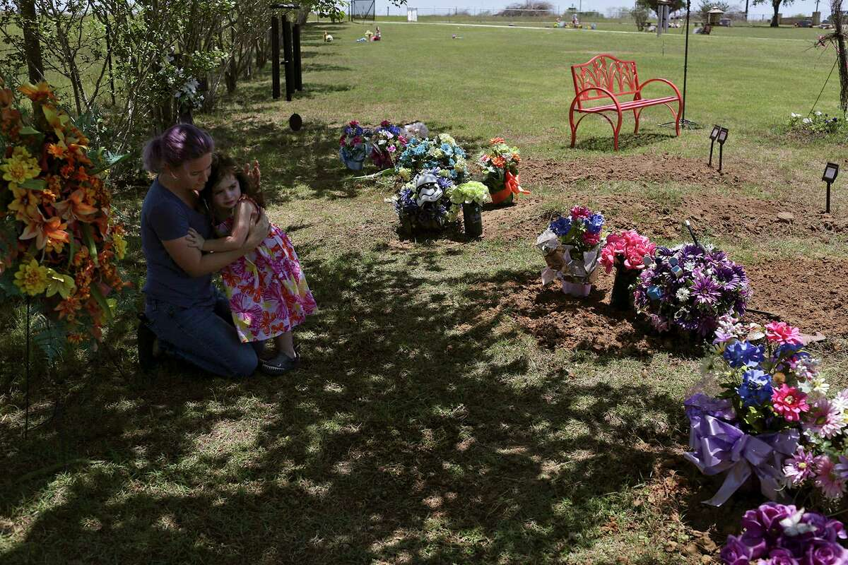 Sarah Slavin holds her daughter, Elene, 3, as Sarah works to take care of the area of the cemetery where nine members of her family and one of her best friends, Tara McNulty, are buried together on May 27.