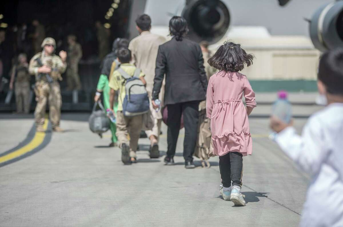 Families board a U.S. Air Force Boeing C-17 Globemaster III during the evacuation at Hamid Karzai International Airport in Kabul on Aug. 23.