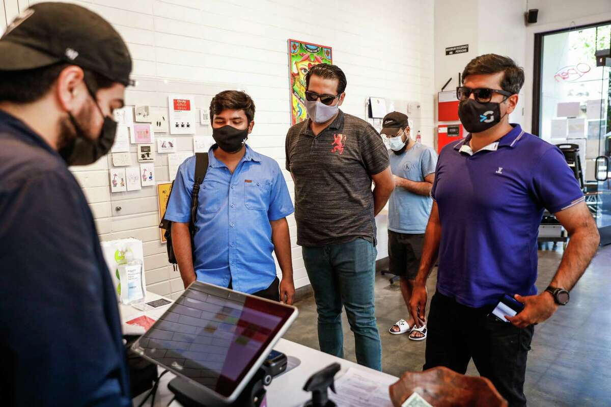 Rameel Farooqi (left) takes an order at Zareen's restaurant in Redwood City. Some Bay Area counties are signaling that they could soon ease up on indoor mask requirements for vaccinated people.