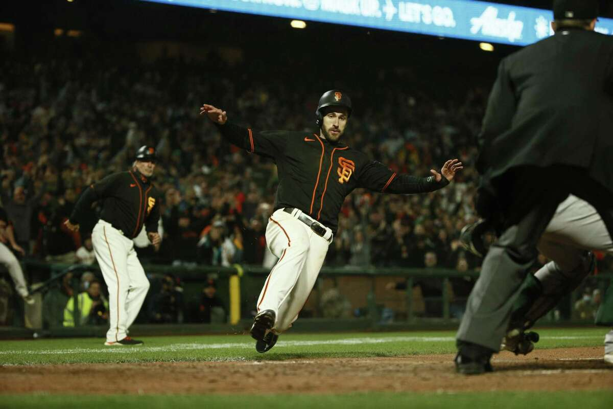 The Giants' Steven Duggar scores the winning run in the 10th inning on a double by Curt Casali to beat the A's 6-5 on June 26.