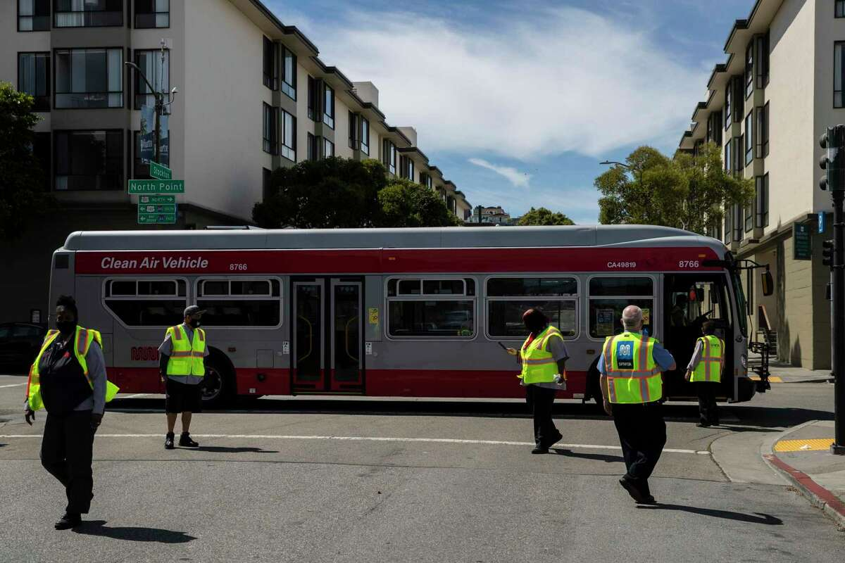 San Francisco Muni workers are seen outside the Kirkland bus yard during a press conference in June. Unvaccinated employees in the transit agency could mean reduced service by Nov. 1.