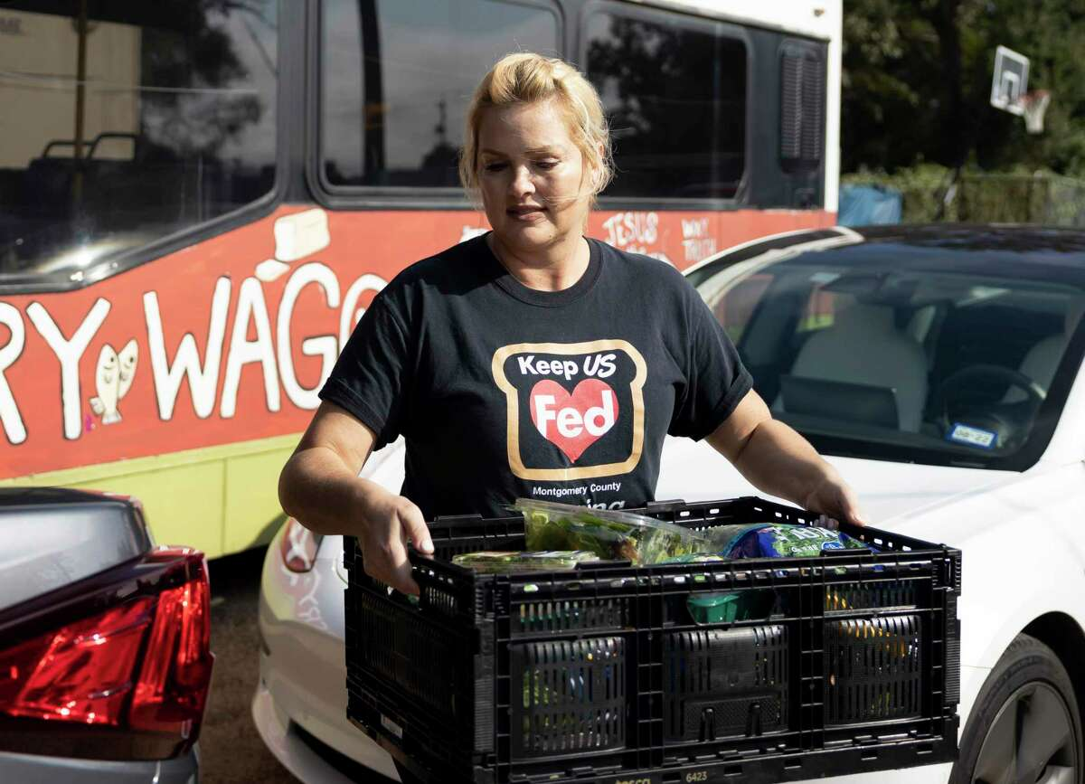 Tiffany Baumann Nelson, executive director of Keep US Fed Montgomery County, unloads a crate of food from the back of her vehicle during a food donation delivery by Keep US Fed Montgomery County at Under Over Fellowship, Thursday, Sept. 30, 2021, in Conroe. Nelson is a breast cancer survivor who was partially inspired by her cancer journey to get involved with philanthropy and start her own organization.