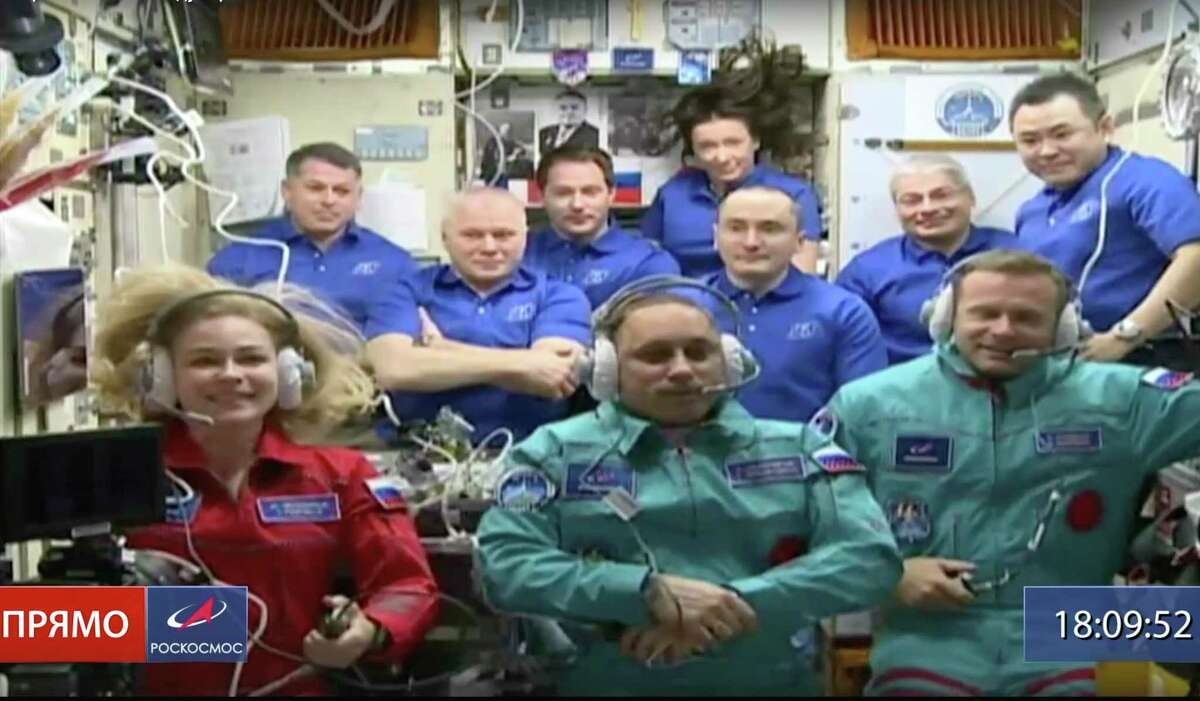 In this photo taken from video footage released by Roscosmos Space Agency, actress Yulia Peresild, left, film director Klim Shipenko, right, and cosmonaut Anton Shkaplerov sit in the first row among other participants of the mission in the International Space Station, ISS, Tuesday, Oct. 5, 2021. Russian actress Yulia Peresild and a film director Klim Shipenko rocketed to space Tuesday on a mission to make the world's first movie in orbit, a project the Kremlin said will help burnish the nation's space glory. (Roscosmos Space Agency via AP)