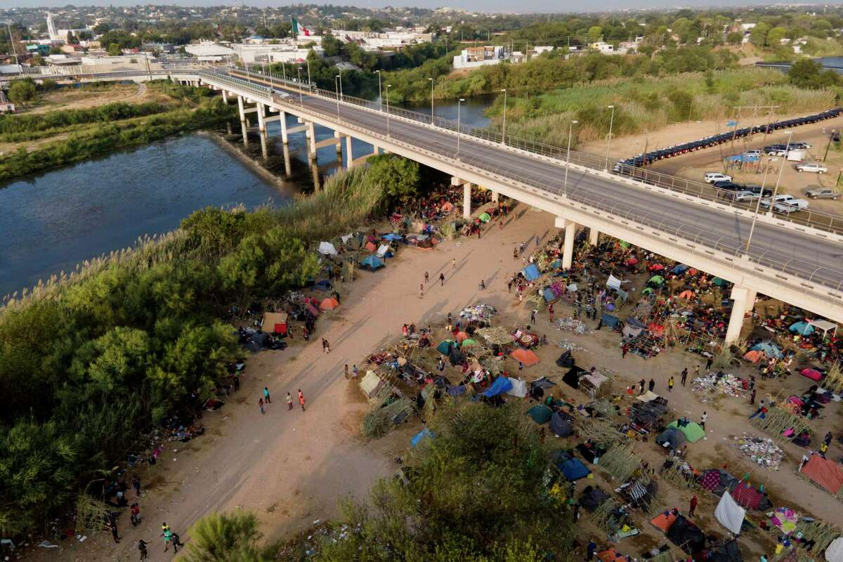 FILE - In this Tuesday, Sept. 21, 2021, file photo, migrants, many from Haiti, are seen at an encampment along the Del Rio International Bridge near the Rio Grande in Del Rio, Texas. The U.S. flew Haitians camped in a Texas border town back to their homeland and blocked others from crossing the border from Mexico. On Friday, the camp on the U.S. side that once held as many as 15,000 mostly Haitian refugees was completely cleared.
