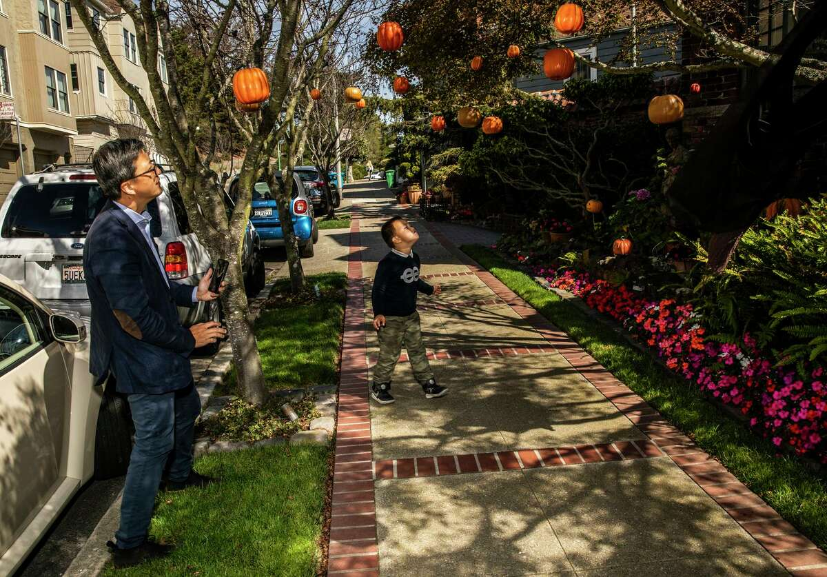 A father and son look at a home with Halloween decorations in the Buena Vista neighborhood of San Francisco.
