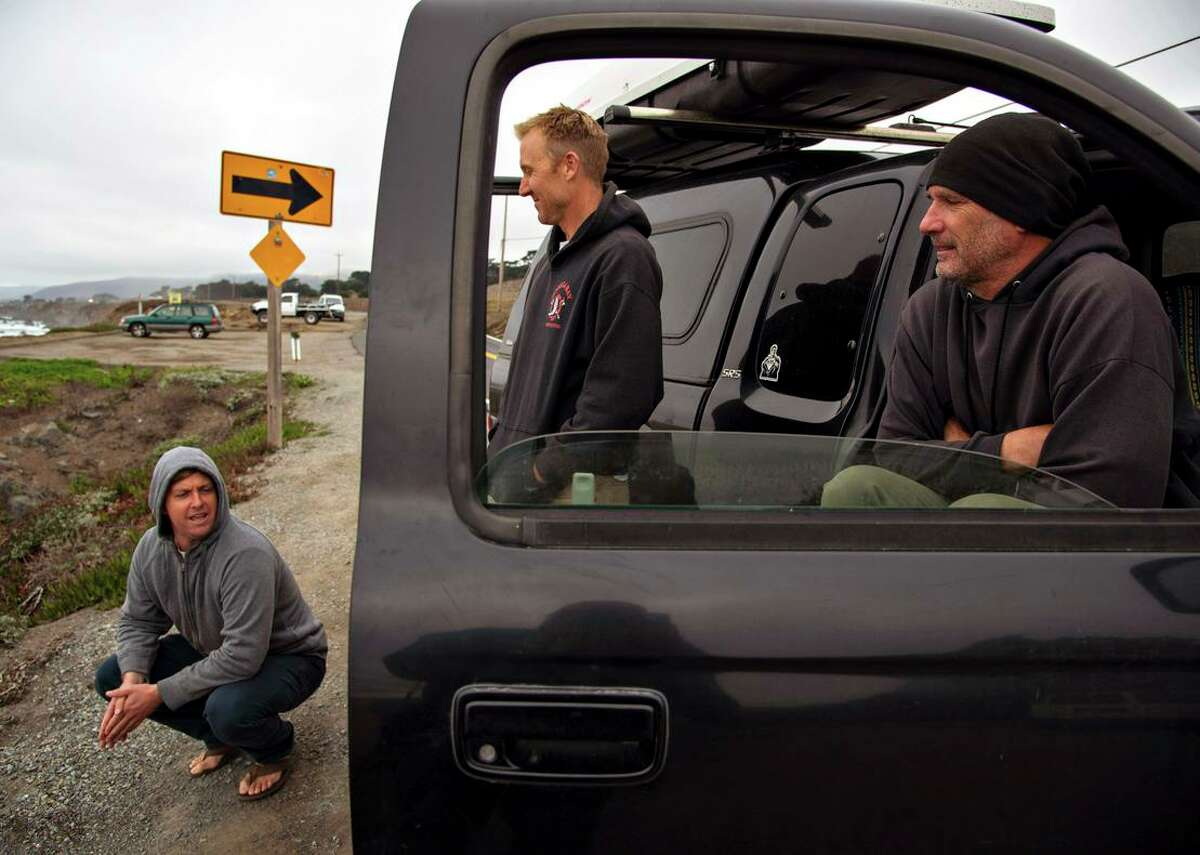 Surfers Travis Vail (left) Heath Lesik and their friend Billy, who declined to provide his last name, watch the surf at North Salmon Creek Beach.