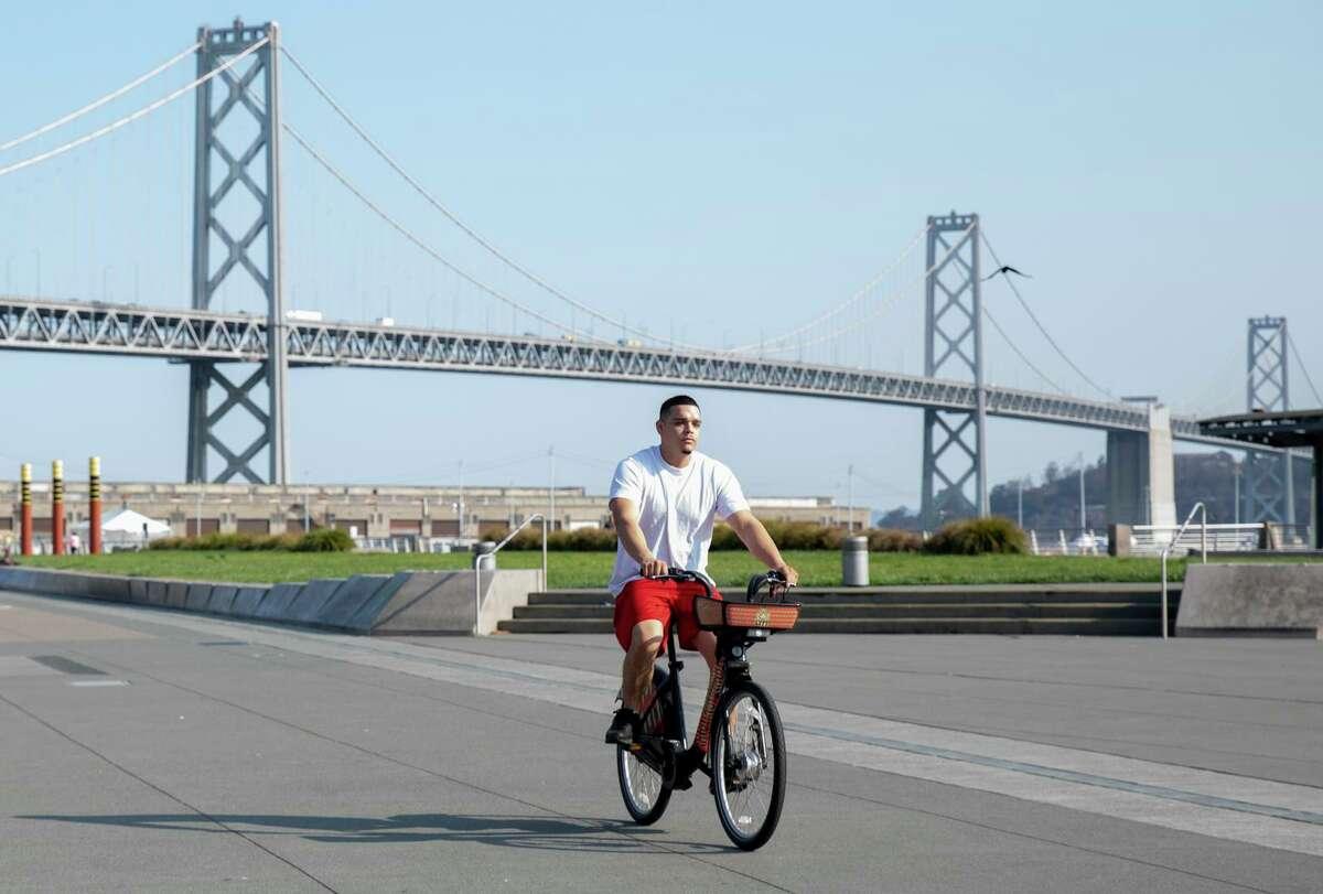 A person rides a Bay Wheels bike along the Embarcadero in San Francisco.