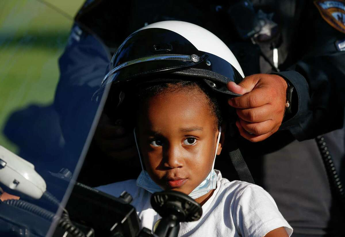 Kymanie Dennis, 4, tries on a helmet while sitting on the motorcycle of a Harris County Sheriff's Office deputy, during the 38th annual National Night Out at Tom Wussow Park on Tuesday, Oct. 5, 2021, in Houston.