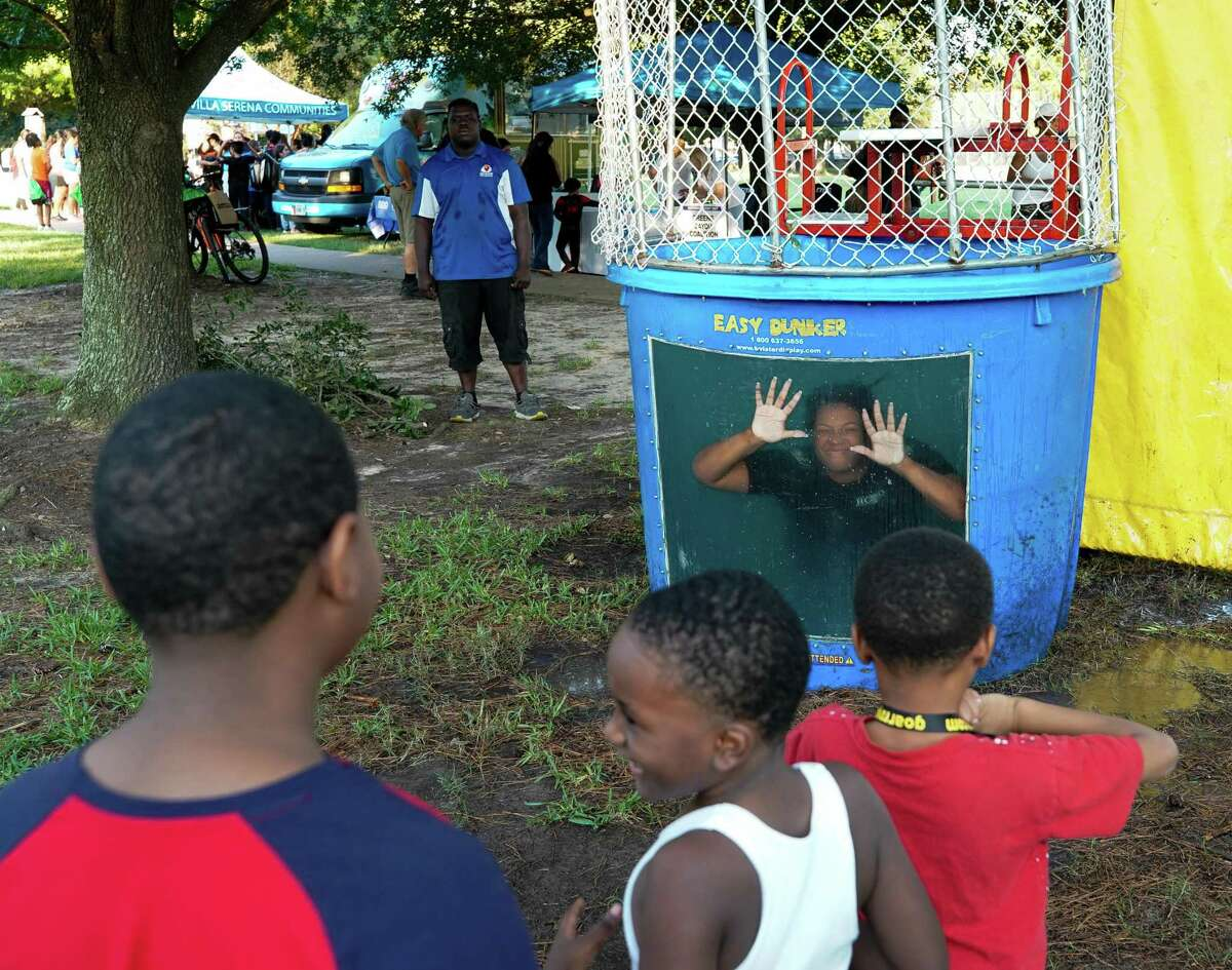 Harris County Sheriff's Office deputy Tiffany Pickens says hi to children in line after she was dunked in the water, during the 38th annual National Night Out at Tom Wussow Park on Tuesday, Oct. 5, 2021, in Houston.