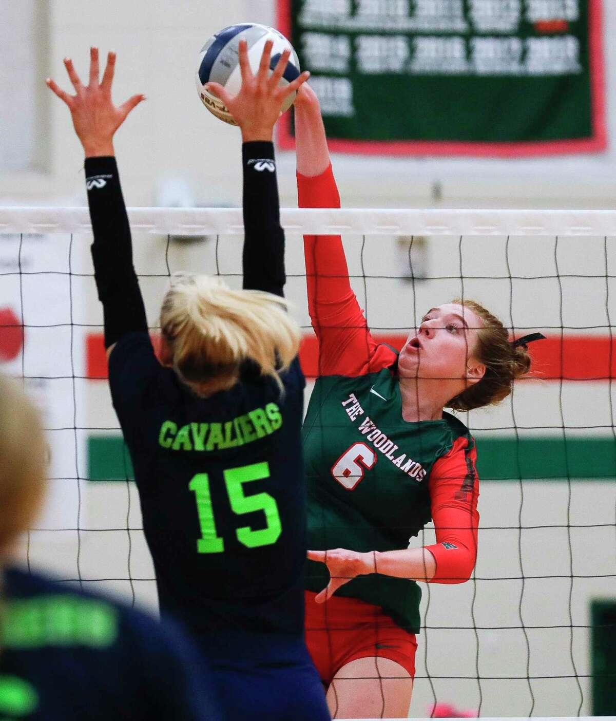 The Woodlands' Reagan Whatley (6) gets a shot past College Park's Paige Bernstein (15) during the first set of a high school volleyball match at The Woodlands High School, Tuesday, Oct. 5, 2021, in The Woodlands.