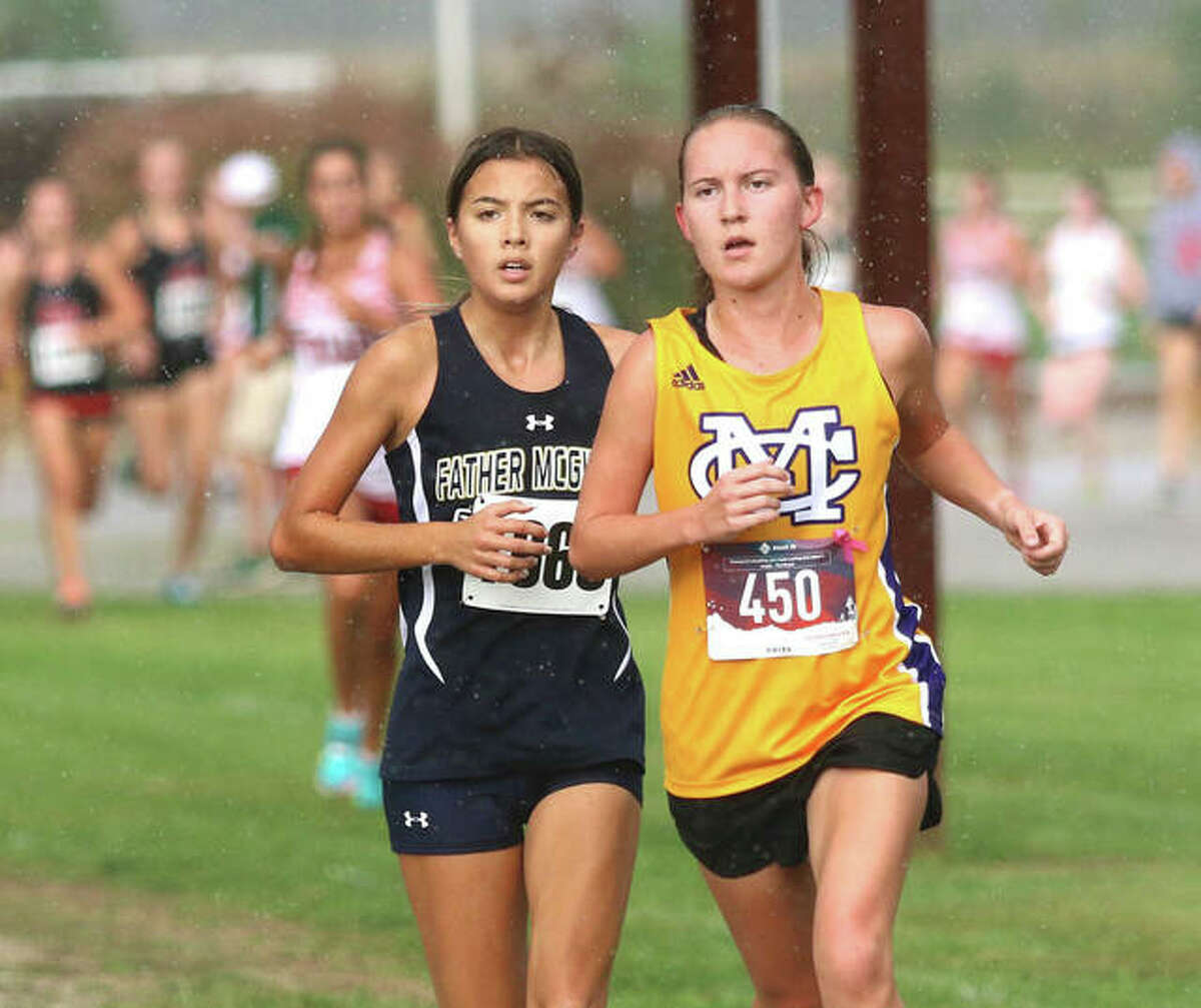 Father McGivney's Kaitlyn Hatley (left) runs off the shoulder of CM's Hannah Meiser as the rain falls during the opening mile of the Madison County Meet on Tuesday at the Bethalto Sports Complex.