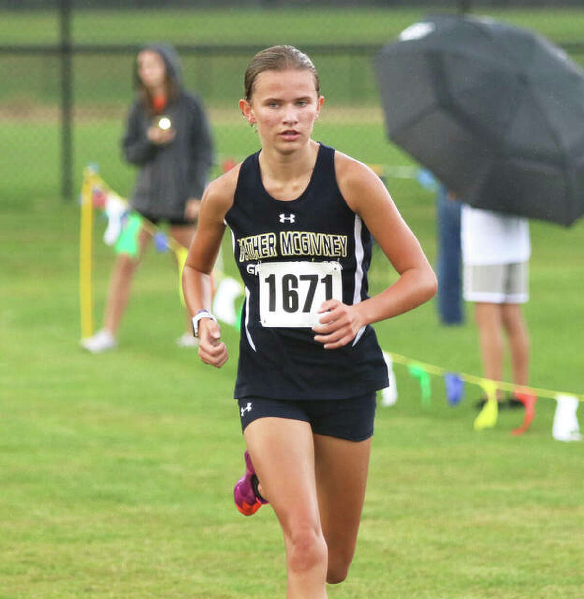 Father McGivney freshman Elena Rybak runs alone on the lead near the finish in her Madison County Meet victory on Tuesday at the Bethalto Sports Complex.