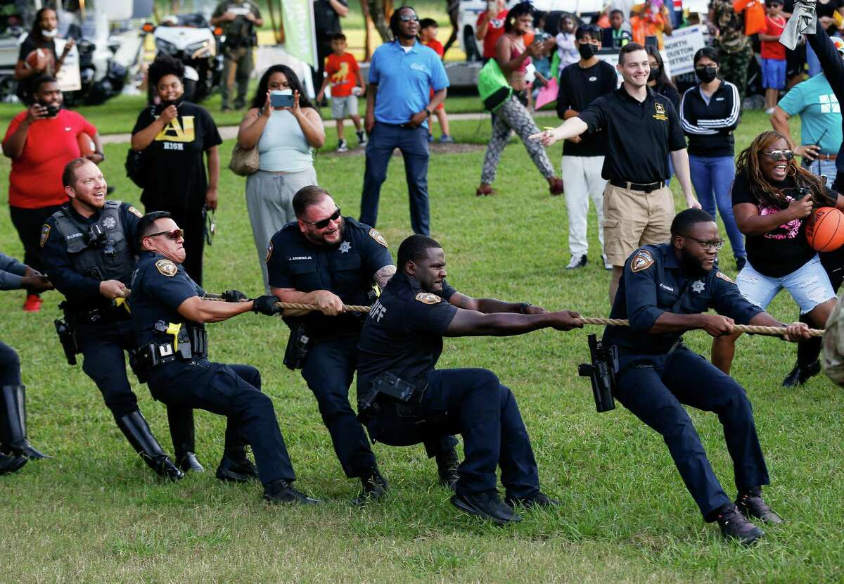 Harris County Sheriff's Office deputies compete in a tug-of-war against Houston Police Department officers during the 38th annual National Night Out at Tom Wussow Park on Tuesday, Oct. 5, 2021, in Houston.