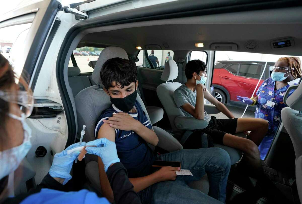 Stephanie Garcia, left, and Jasmine Blackmon, right, both medical assistant, prepare to give Bahir Naseri, 14, second from left, and his brother, Shabir Naseri, 16, their second COVID-19 vaccination at Dick Graves Park, 2000 Reed Road, Thursday, Sept. 23, 2021 in Houston. The brothers from Afghanistan are in the reVision program. The faith-based nonprofit that works with at-risk, homeless, refugee youth, has come up with a new way to encourage teens to get vaccinated by using student ambassadors. The organization found that teens respond better when their peers ask them to get the shot, instead of an adult.