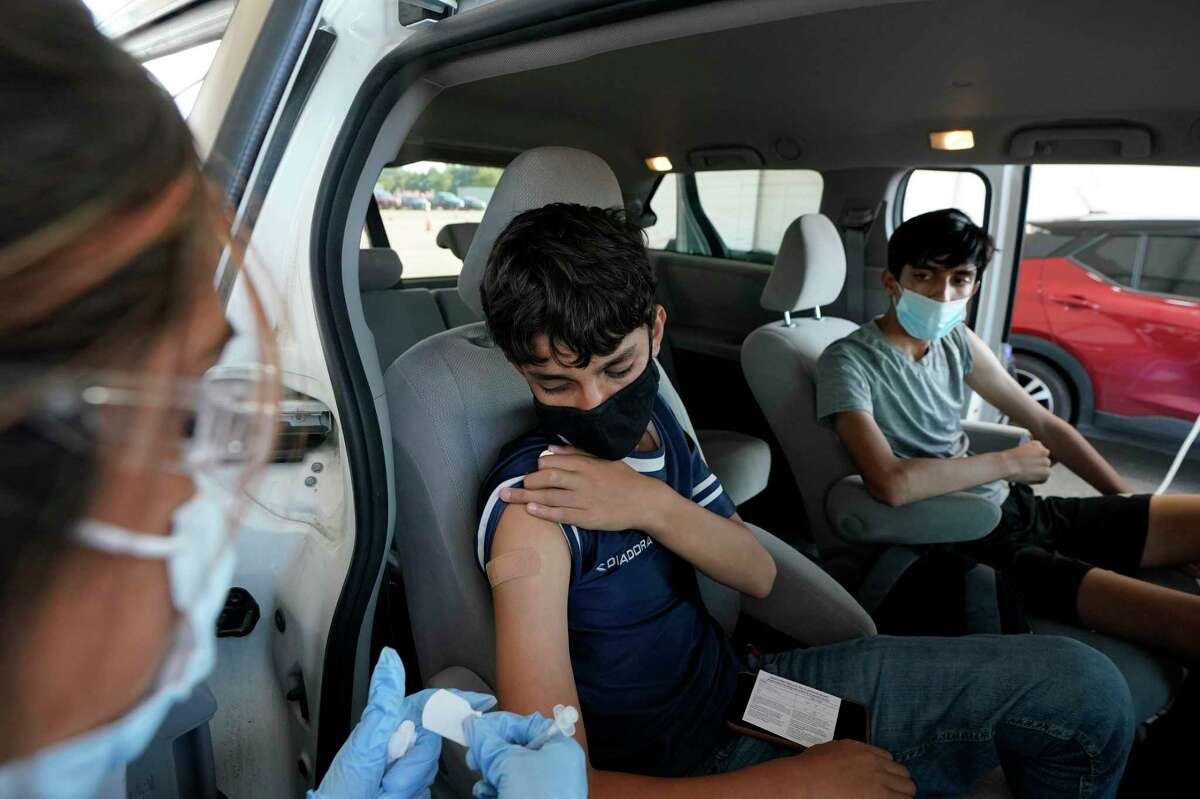 Stephanie Garcia, left, a medical assistant, prepares to give Bahir Naseri, 14, a COVID-19 vaccination as his brother, Shabir Naseri, 16, watches at Dick Graves Park, 2000 Reed Road, Thursday, Sept. 23, 2021 in Houston. The brothers from Afghanistan are in the reVision program. The faith-based nonprofit that works with at-risk, homeless, refugee youth, has come up with a new way to encourage teens to get vaccinated by using student ambassadors. The organization found that teens respond better when their peers ask them to get the shot, instead of an adult.
