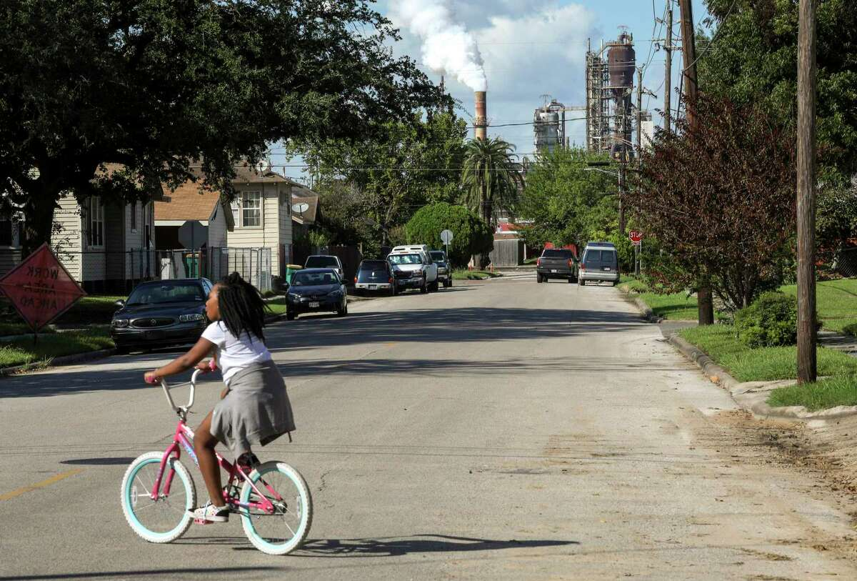 """Rhianna Winslow, 9, rides her bike in front of her house on Oklahoma Street on Tuesday, Sept. 24, 2019, in Baytown. Winslow said """"it stank"""" the previous week."""