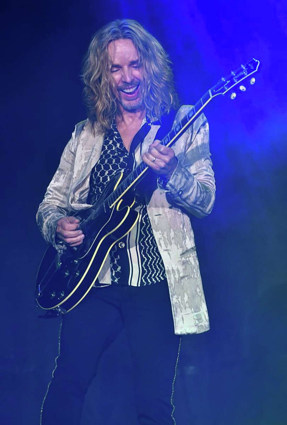 """Singer, songwriter and guitarist Tommy Shaw of the rock band Styx is shown having fun on stage during the groups """"live"""" concert appearance at The Big E in West Springfield, Massachusetts on Oct. 3, 2021."""
