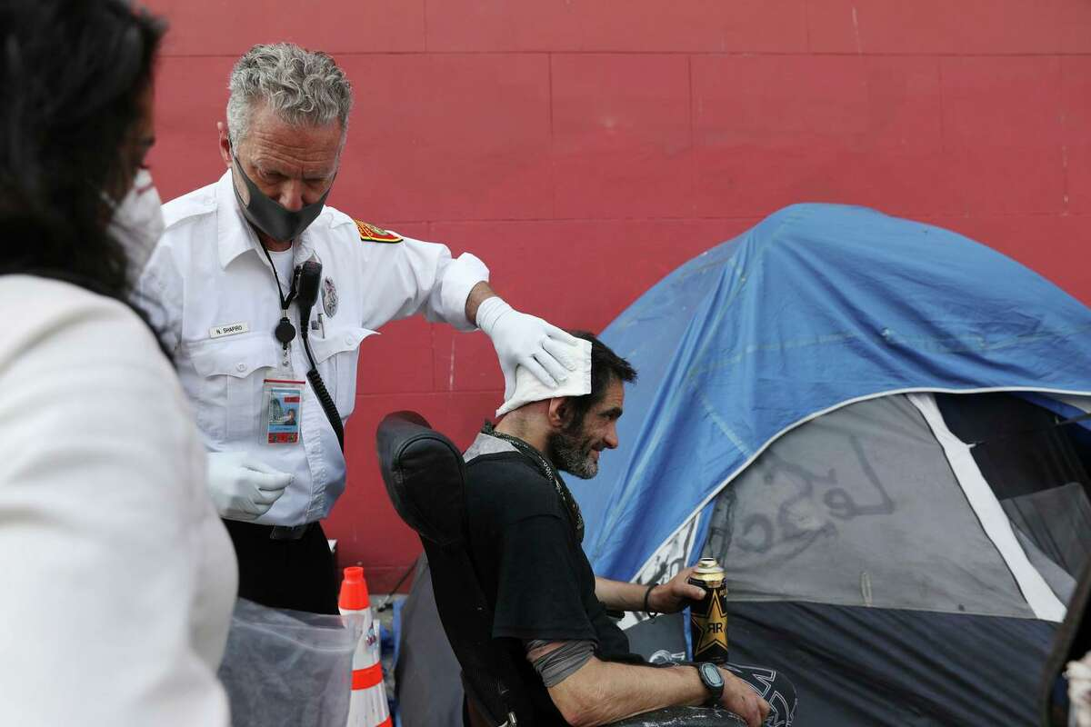 Acting rescue Captain of the Healthy Streets Operations Center Nathan Shapiro (second from left) tends to a head wound of Ariel Fortuna (right) outside Fortuna's tent at a homeless encampment on 19th Street on Friday, August 27, 2021 in San Francisco, Calif.