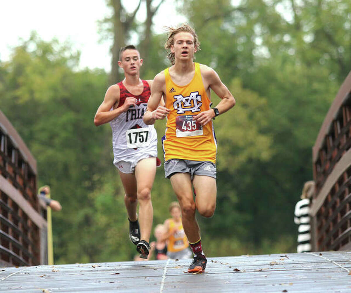 CM's Jackson Collman (right) leads Triad's Andrew Pace over the bridge at the Bethalto Sports Complex during the Madison County cross country meet on Tuesday in Bethalto. Collman won the race, with Pace placing second.