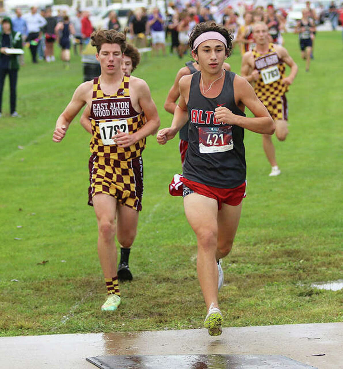 Alton's Alex Macias (front) leads EA-WR's Aidan Loeffelman (left) onto the bridge in the second mile of the Madison County Meet on Tuesday at the Bethalto Sports Complex.