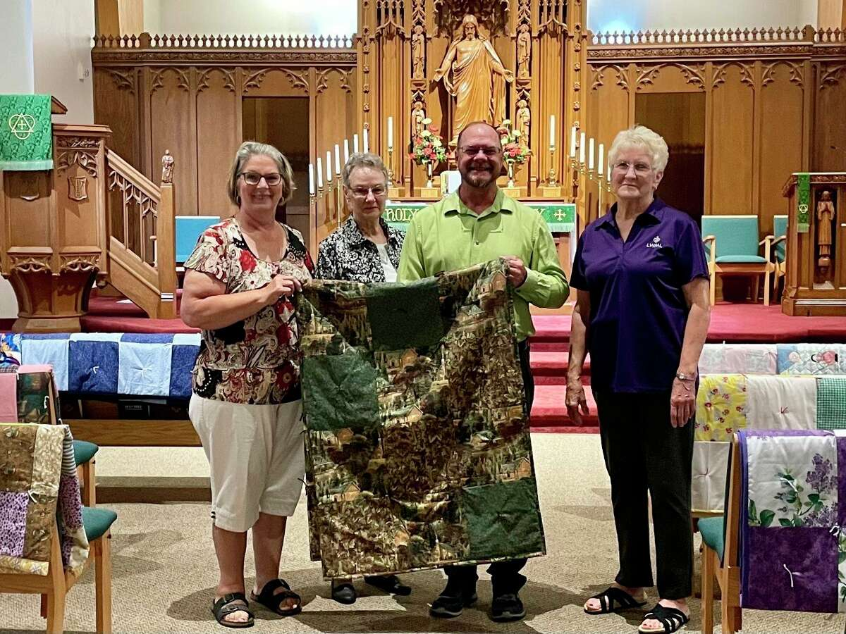 Trinity Lutheran School teacher, Ric Genthner received a free quilt from LWML members during the recent Sunday service, as part of the Trinity tradition of providing new teachers with a handmade quilt. Pictured, from left to right, areRosalee Donley, Marie Keller, Ric Genthner and Peggy Graham. (Submitted photo)