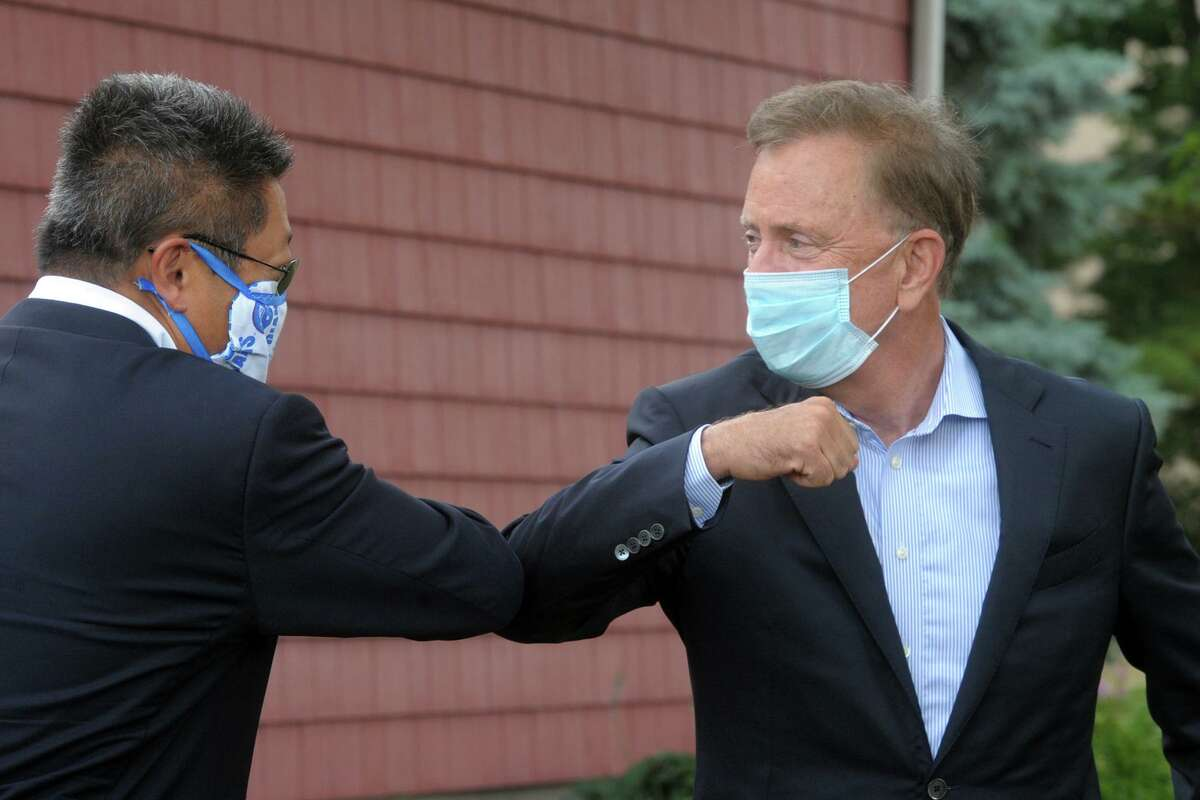 Gov. Ned Lamont bumps elbows with State Sen. Tony Hwang on the University of Bridgeport campus, in Bridgeport, Conn., June 30, 2020.