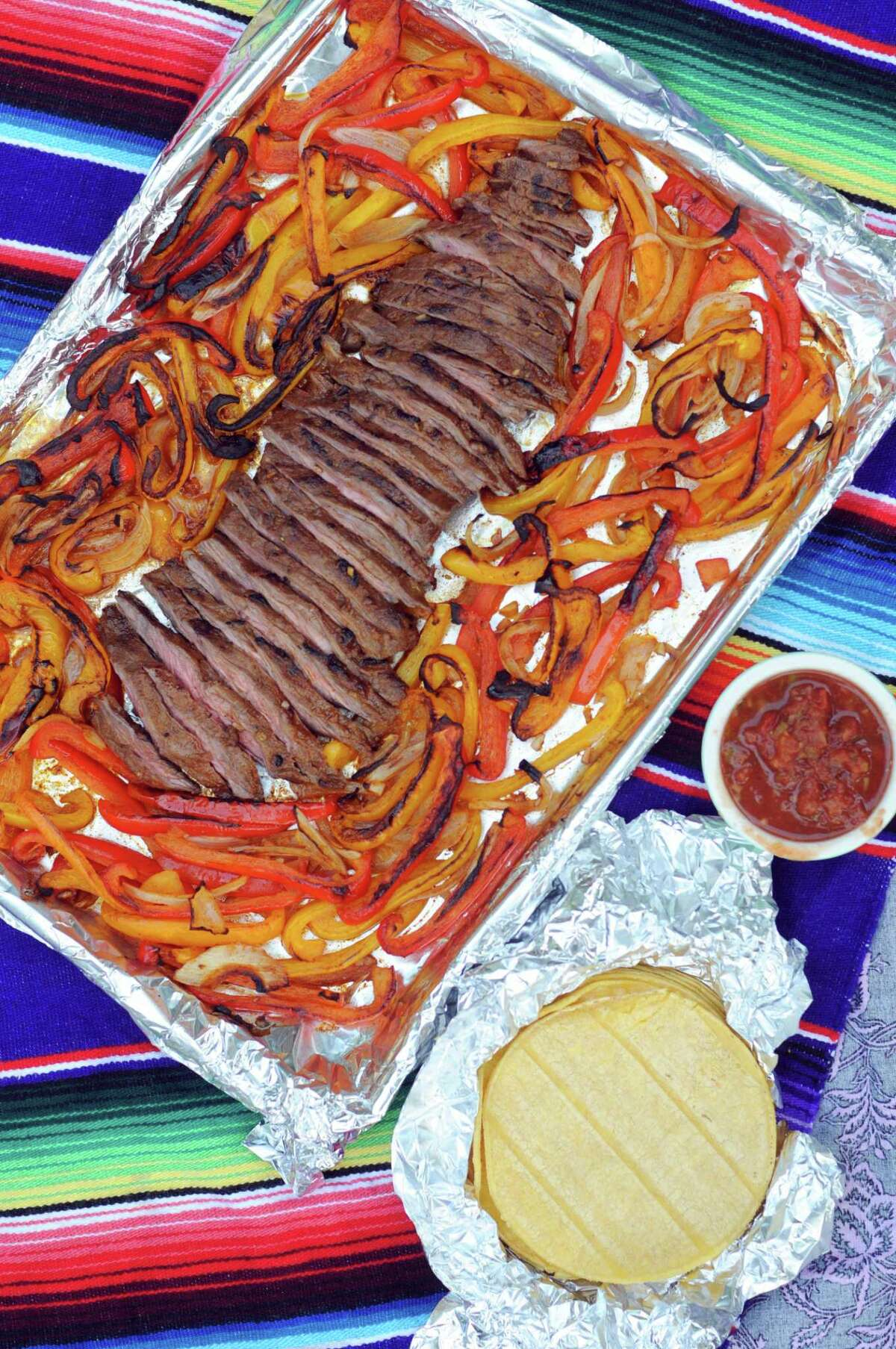 Dinners such as Sheet Pan Fajita Flank Steak with Peppers and Onions are easy to make and deliver bold flavors. Recipe, Page E8.