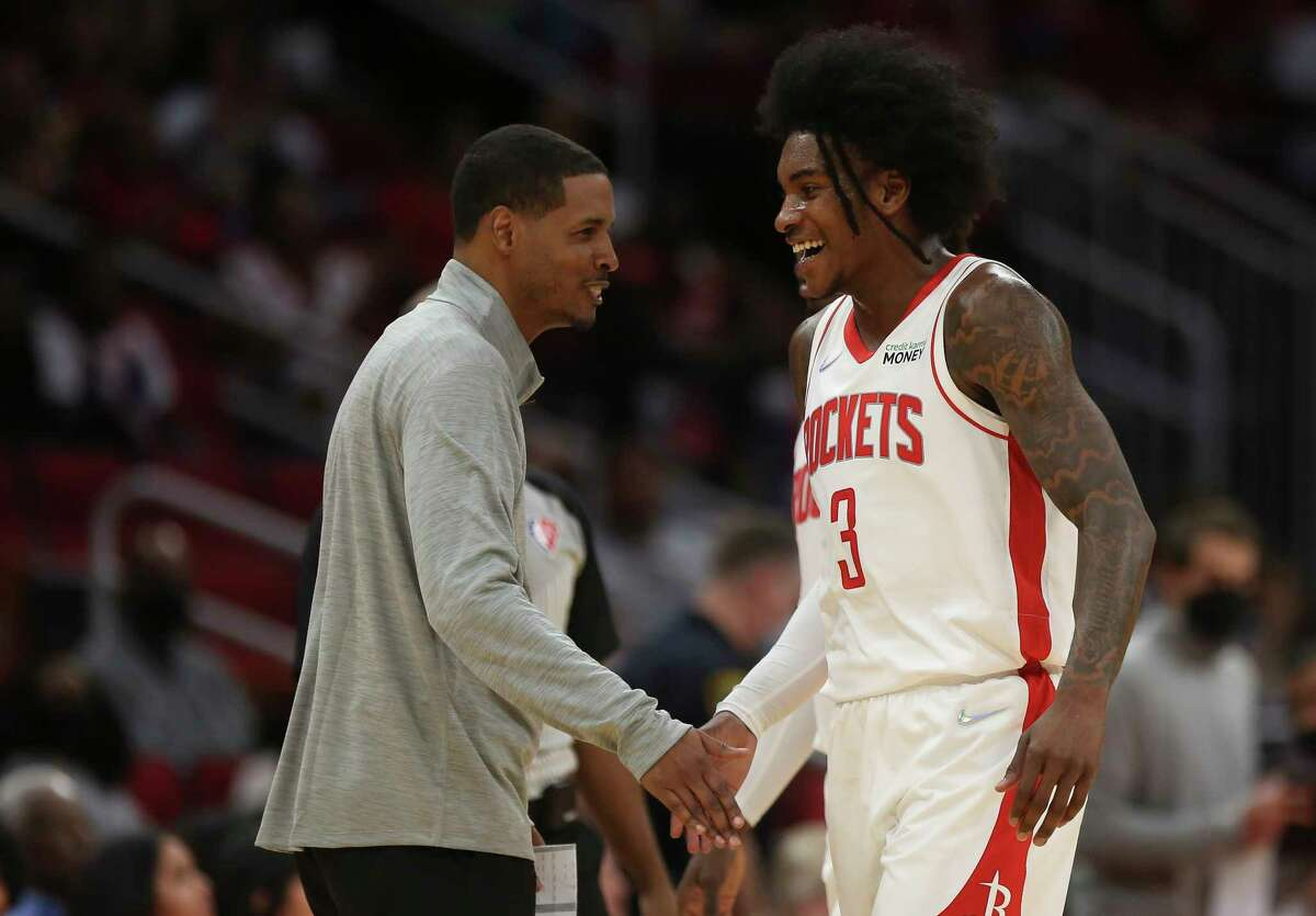 Houston Rockets head coach Stephen Silas and guard Kevin Porter Jr. (3) share a low-five during the first half of the NBA game against the Washington Wizards Tuesday, Oct. 5, 2021, at Toyota Center in Houston.