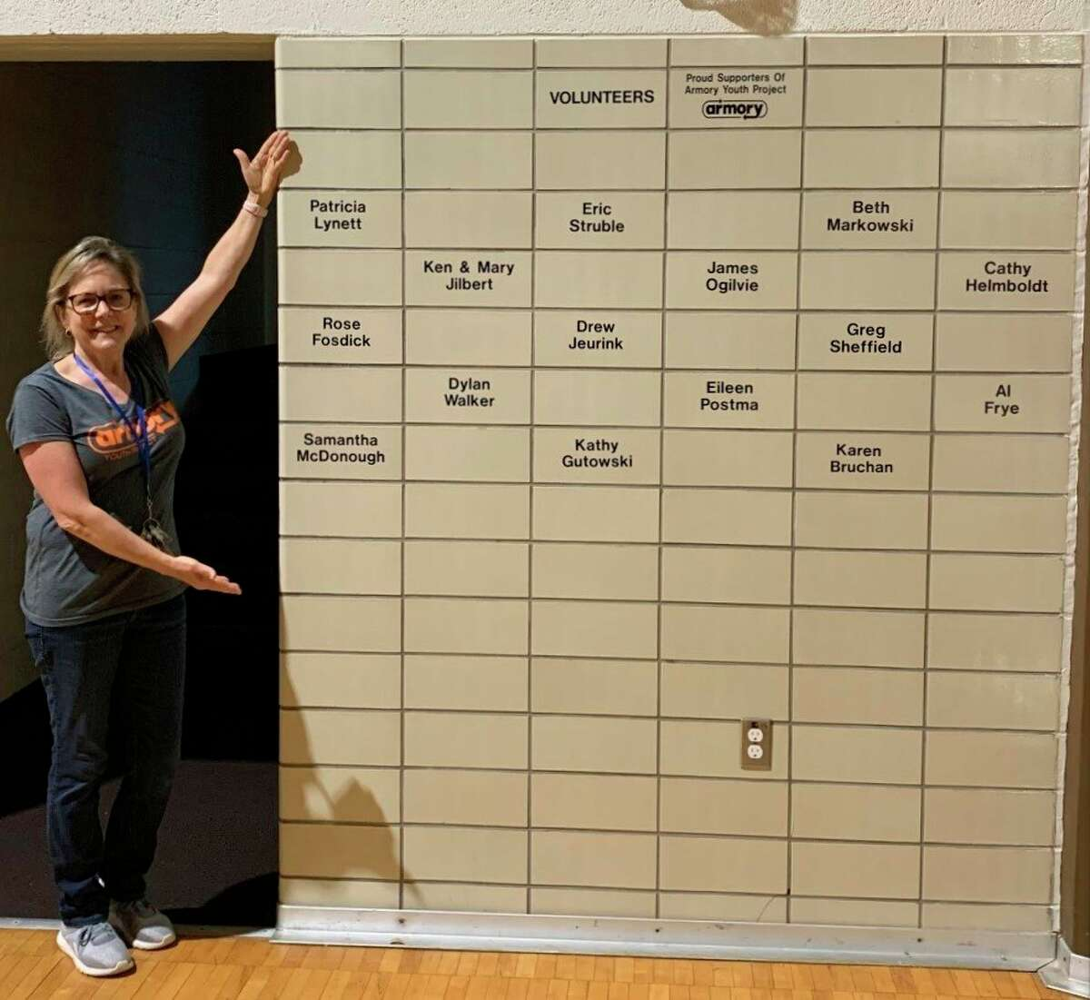 Amy Wojciechowski, Armory Youth Project executive director, shows off the Wall of Service which features the names of volunteers who have provided over 150 hours of service in the past year. (Courtesy photo)