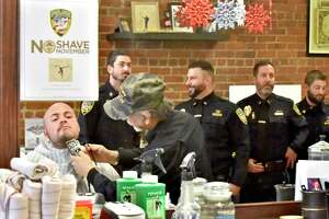 Wallingford, Connecticut - Friday, December 1, 2017: Wallingford Police Detective Steve Jaques (CQ) has his beard shaved by barber Gerardo Fernicola of Dino's Modern Barbershop Friday morning in Wallingford as fellow police officers wait to have their beards shaved during the culmination of the No Shave November fundraising campaign to raise awareness and funding for cancer prevention, education and research. A majority of the Wallingford Police officers participated in the month long campaign which netted $5,716 from the officers.