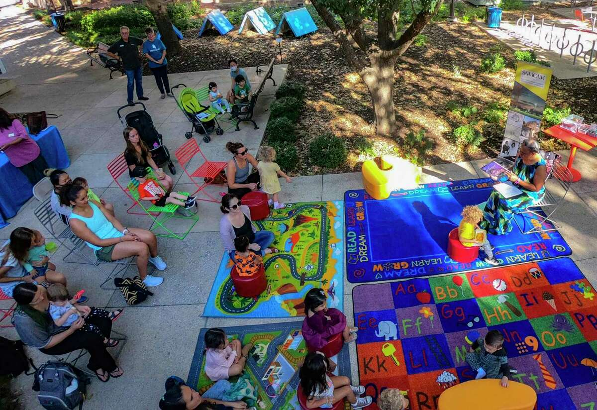 """Children and parents listen at Hemisfair as Sallie Frederick, at top right, a retired elementary school principal, reads """"Sulwe"""" by Lupita Nyong'o as part of the San Antonio African American Community Archive and Museum Story Time series at Yanaguana Garden on Tuesday."""