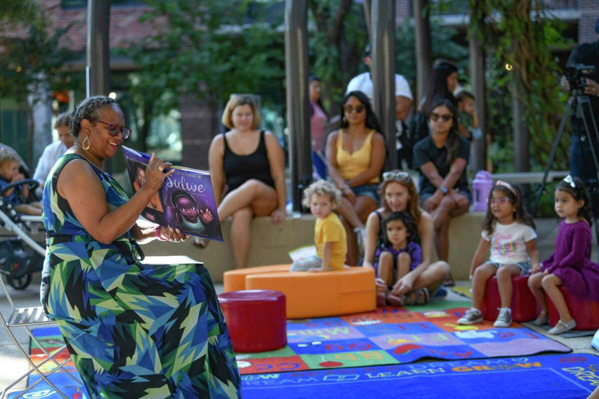 """Sallie Frederick, a retired elementary school principal, reads """"Sulwe"""" by Lupita Nyong'o to children at Hemisfair as part of the San Antonio African American Community Archive and Museum Story Time series at Yanaguana Garden on Tuesday."""