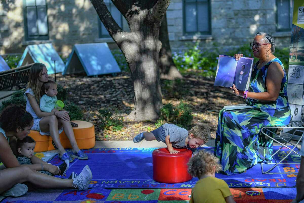 """Sallie Frederick, a retired elementary school principal, reads """"Sulwe"""" by Lupita Nyong'o to children as part of the San Antonio African American Community Archive and Museum Story Time series at Yanaguana Garden at Hemisfair on Tuesday."""