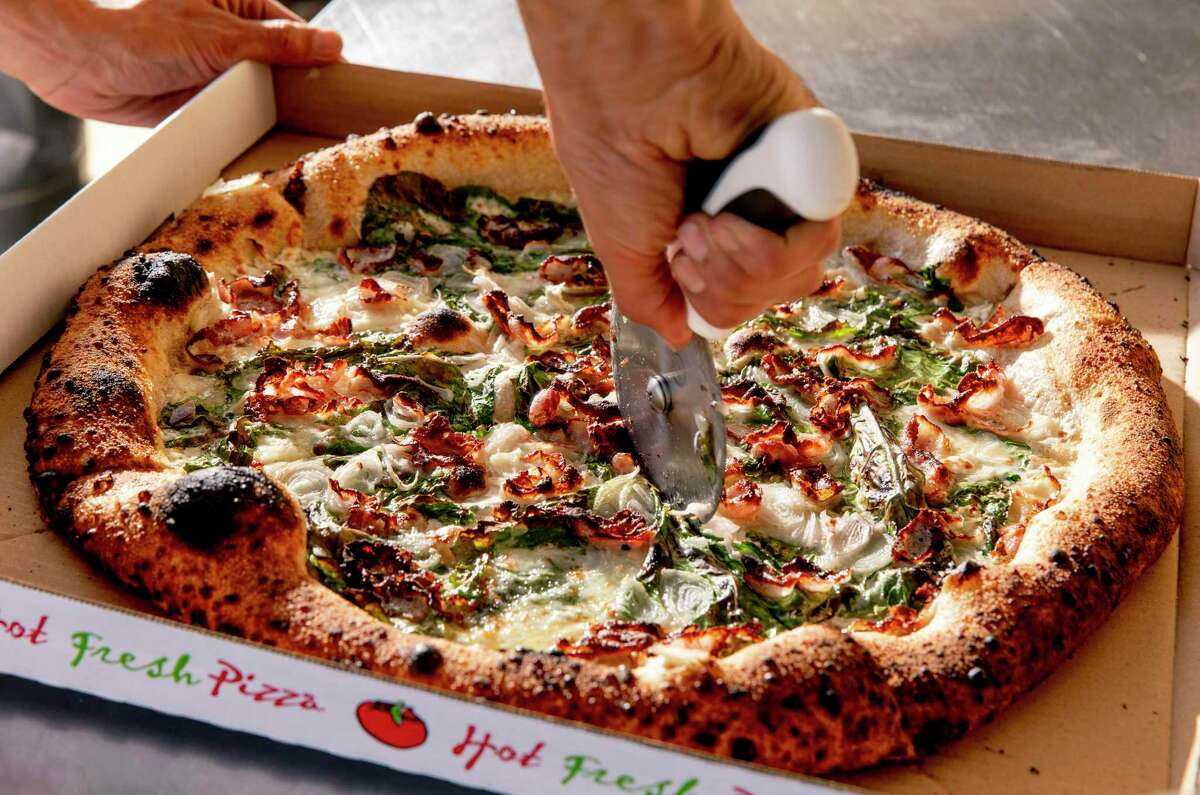 Chef Michael de la Torre adds the final touches to the weekly special pizza (topped with butternut squash, guanciale and karinata kale) at June's Pizza in Oakland, CA on Sunday, October 25, 2020.