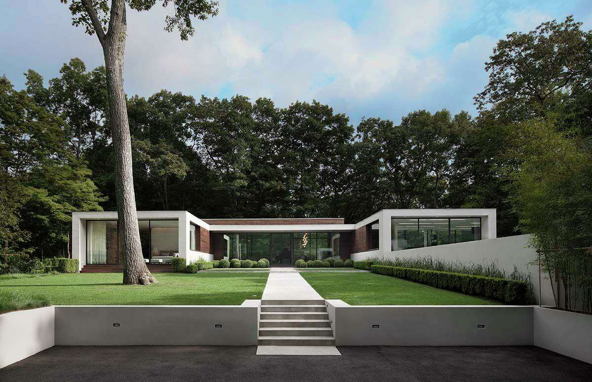 After a winding drive through the trees, you come to an open hilltop court featuring the long, low form of a modern home.