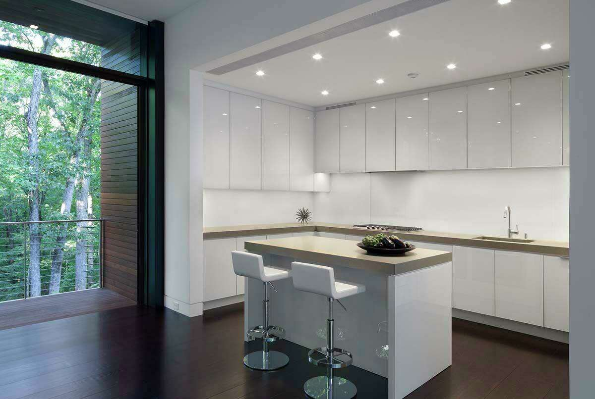 Minimally designed to keep everything hidden, the kitchen is adjacent to the dining area to maintain a connection between the spaces.
