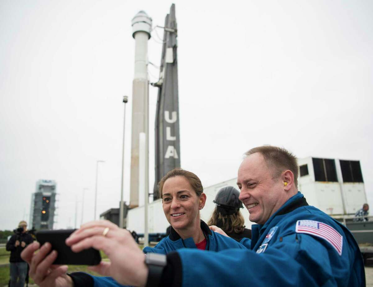 NASA astronauts Nicole Mann, left, and Michael Fincke take a selfie in front of a United Launch Alliance Atlas V rocket with Boeing's CST-100 Starliner spacecraft onboard on Dec. 18, 2019 at Cape Canaveral Air Force Station in Florida. Mann is no longer assigned to fly on Boeing. She has been moved to a SpaceX mission as Boeing continues to troubleshoot issues with its spacecraft valves.