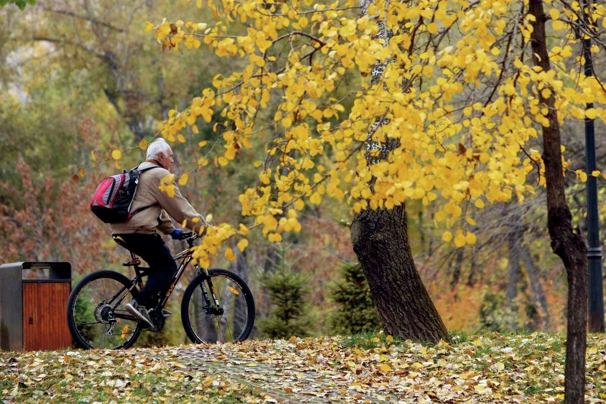 A senior citizenrides a bicycle in a parkin Ukrainein fall 2018. (Photo by Ovsyannikova Yulia / Barcroft Media via Getty Images)