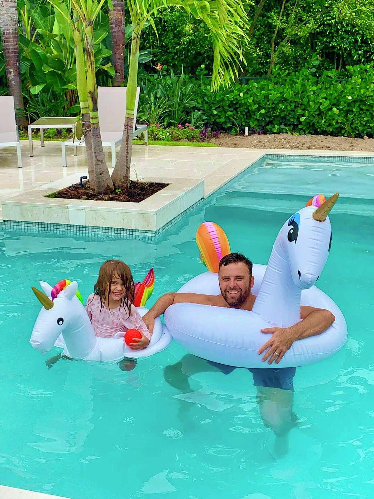 Jonathan Badger juega con su hija Sarah, ahora de 4 años, en la piscina trasera del intercambio de casas donde se quedaron durante el verano de 2020.