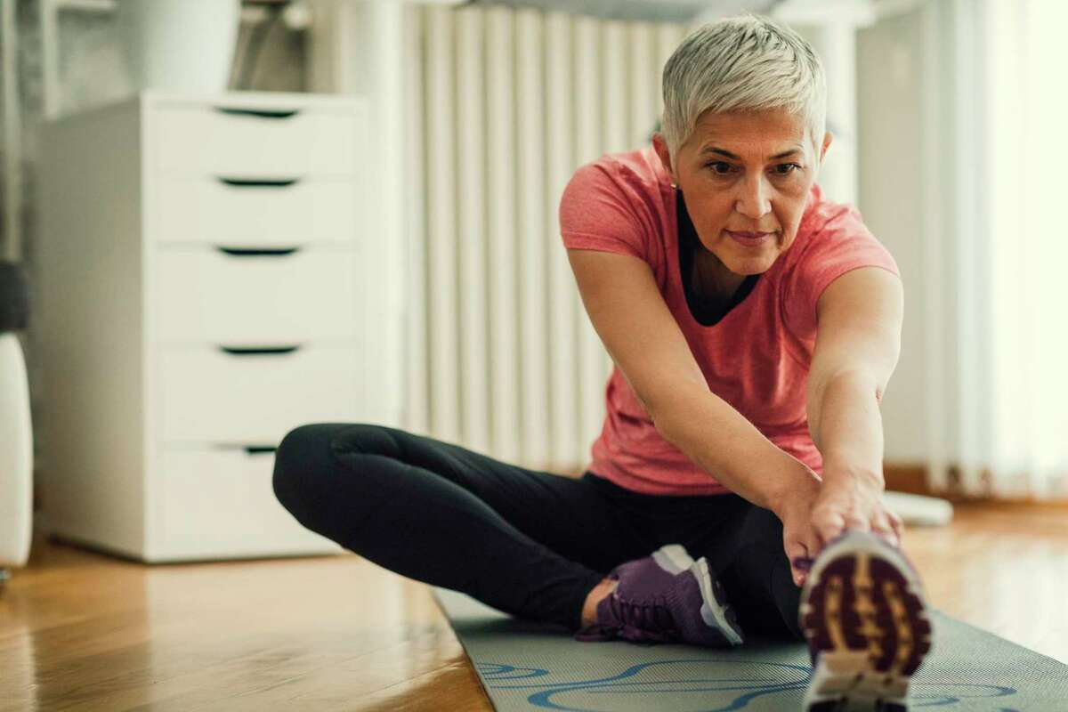 Mature woman exercising at home. Sitting on exercise mat and working stretching exercise , stretching her legs.