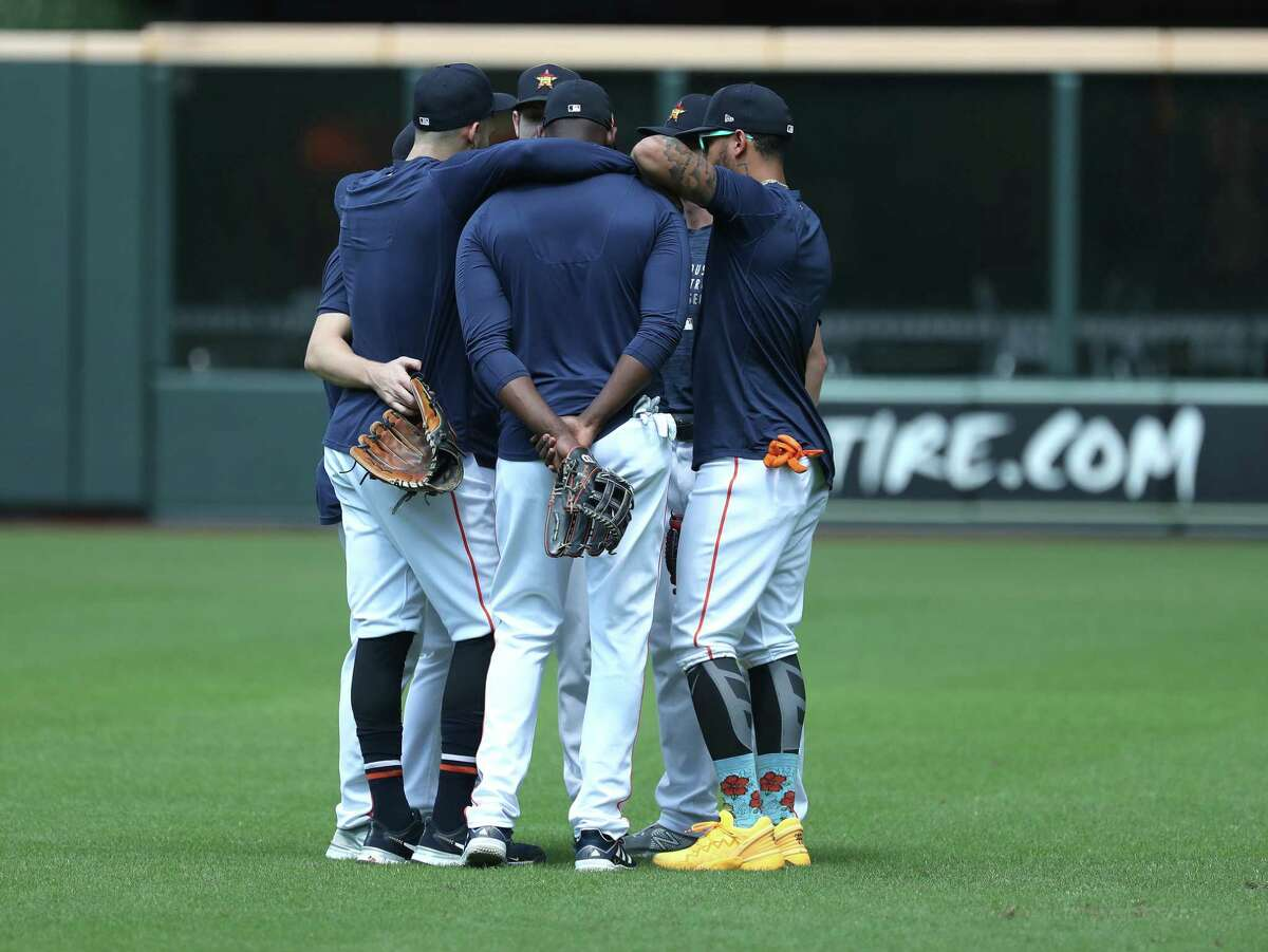 Houston Astros Carlos Correa, left, gathers the outfielders for a huddle during batting practice ahead of Game 1 of the American League Division Series playoffs at Minute Maid Park, Wednesday, Oct. 6, 2021, in Houston.