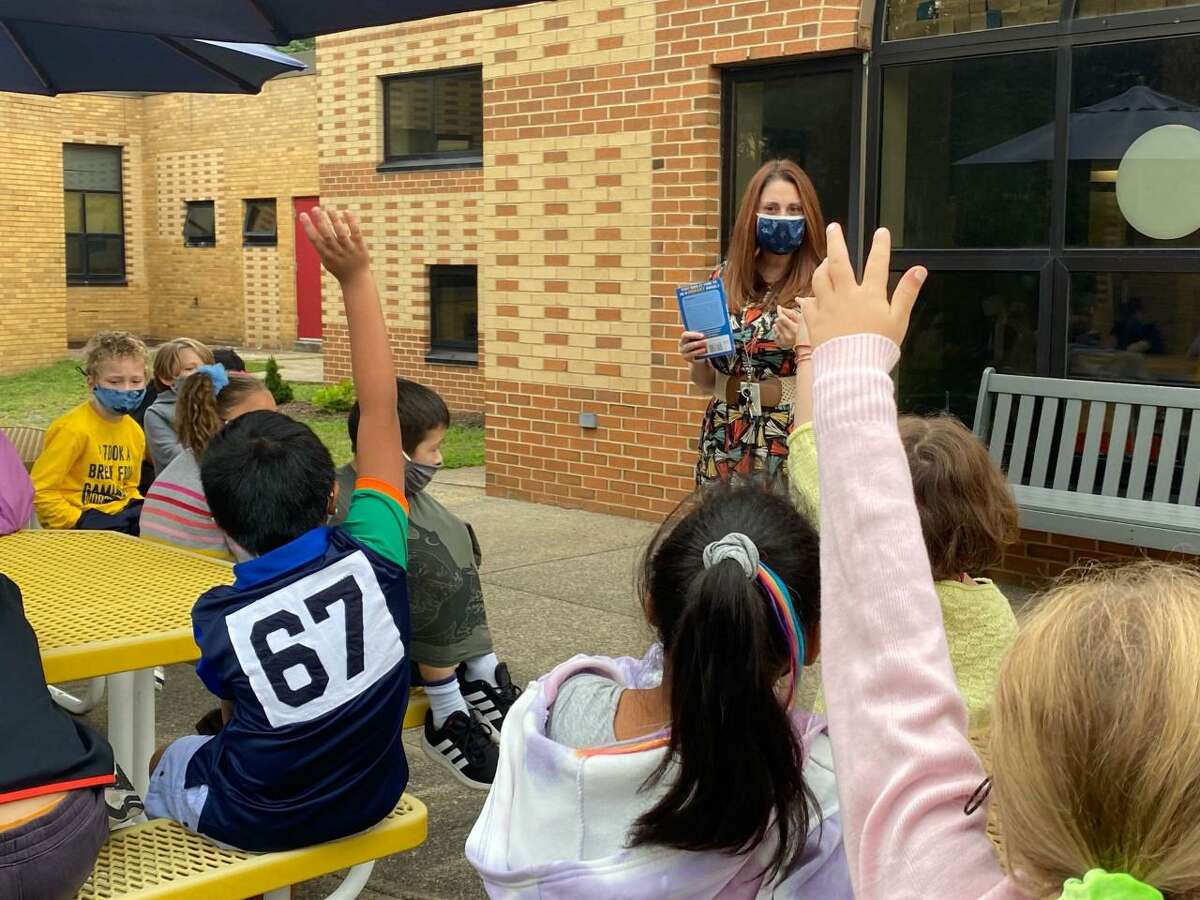 Sunnyside School third grade teacher Allissa Dempsey reads to her class in the school's courtyard. Shelton High senior Joseph Savino rehabbed the school's courtyard, including adding the bench and building new garden boxes, as part of his Eagle Scout project.