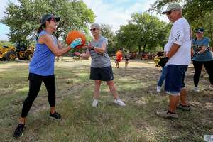 Sherry Kenisky, from left, Janet Tennis and Frank Kenisky pass a pumpkin down an assembly line as volunteers unload 2,300 pumpkins and additional decorative gourds for the Universal City Pumpkin Patch at the Universal City Municipal Building on Sept. 27. The patch is free to visit and is open 3-7 p.m. Monday through Thursday, and 11 a.m.-7 p.m. Friday through Sunday.