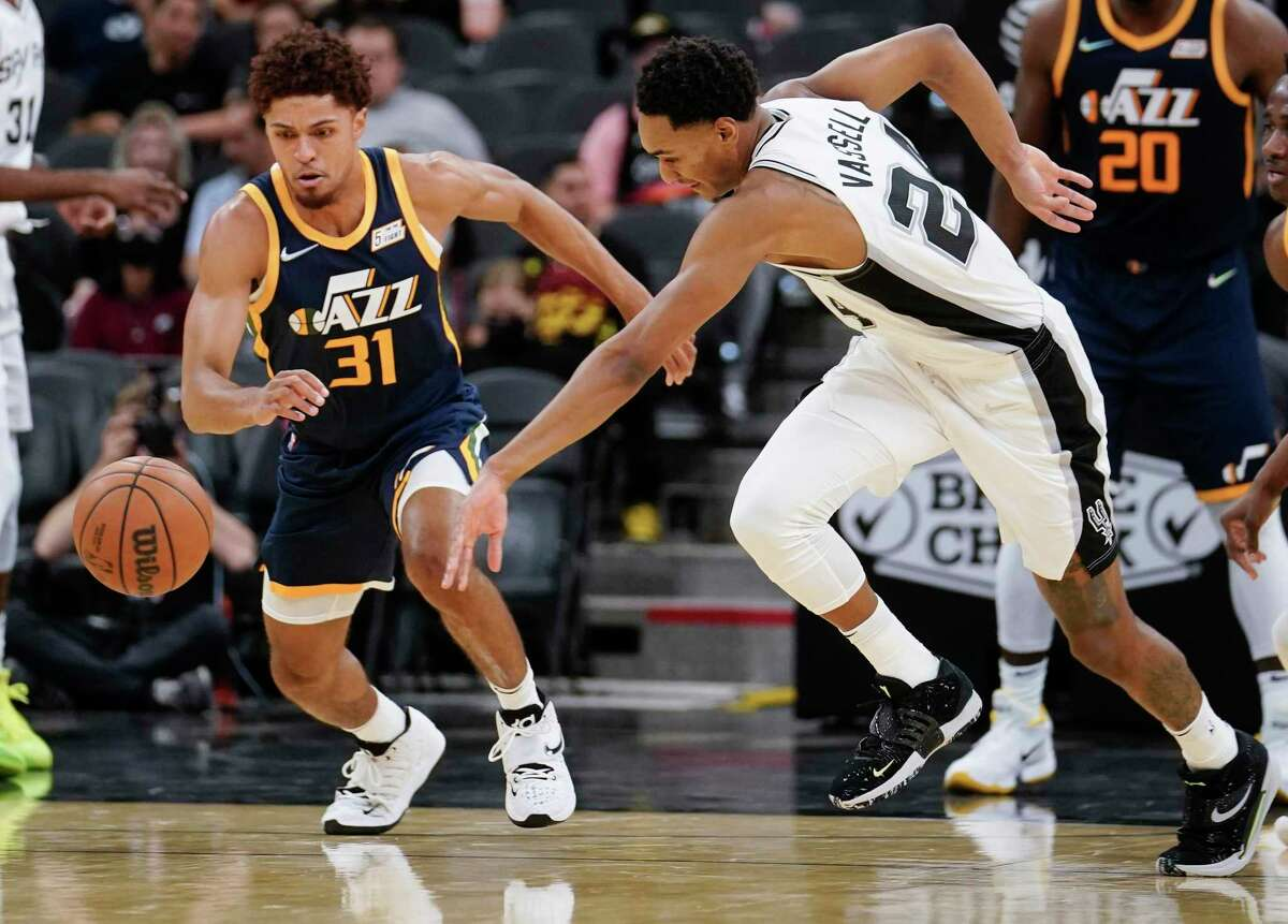 San Antonio Spurs' Devin Vassell, right, and Utah Jazz's MaCio Teague chase the ball during the second half of an NBA basketball game on Monday, Oct. 4, 2021, in San Antonio.