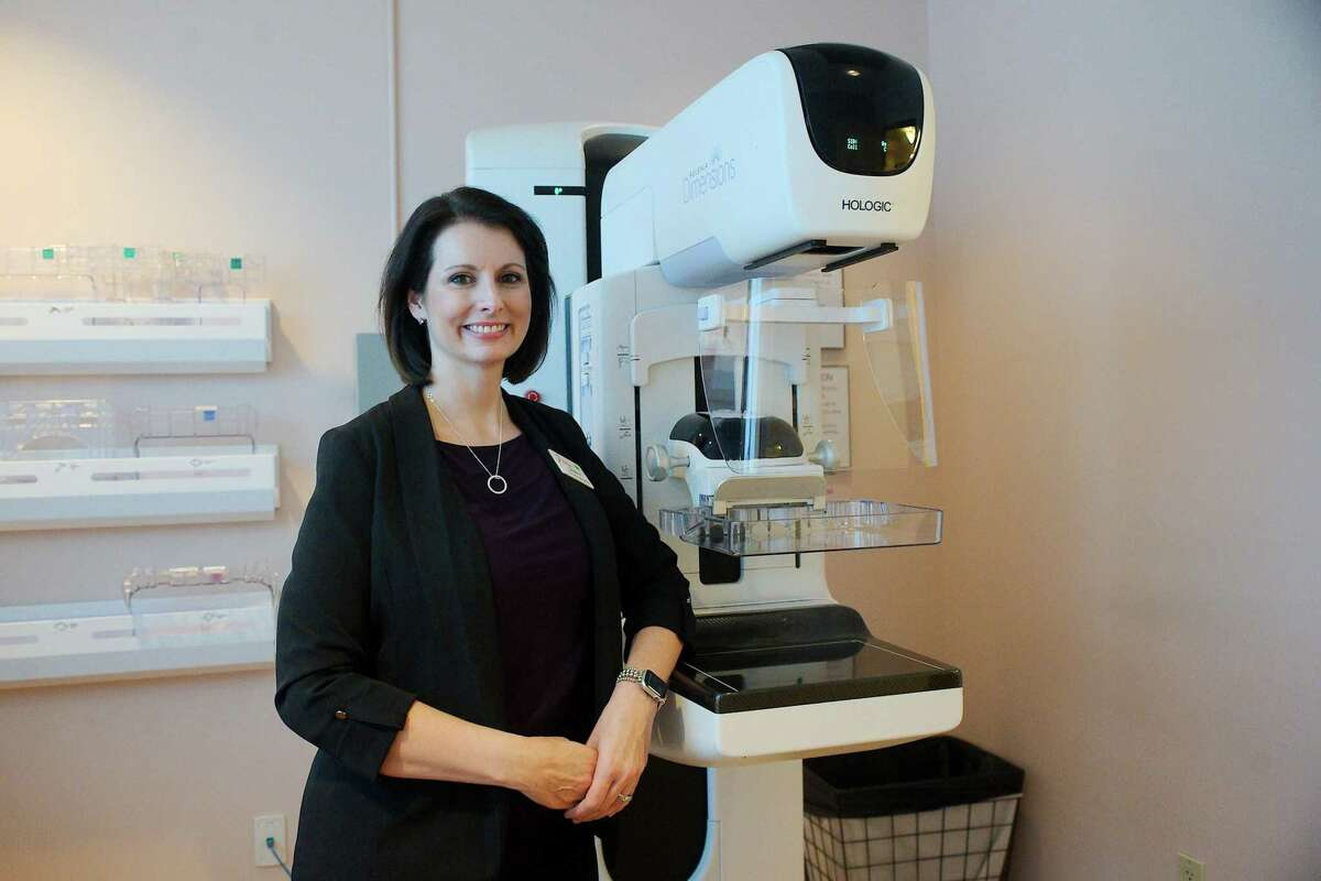 The Rose Chief Administrative Officer Jessica Duckworth stands beside a mammography machine very similar to the one used to diagnose her breast cancer.