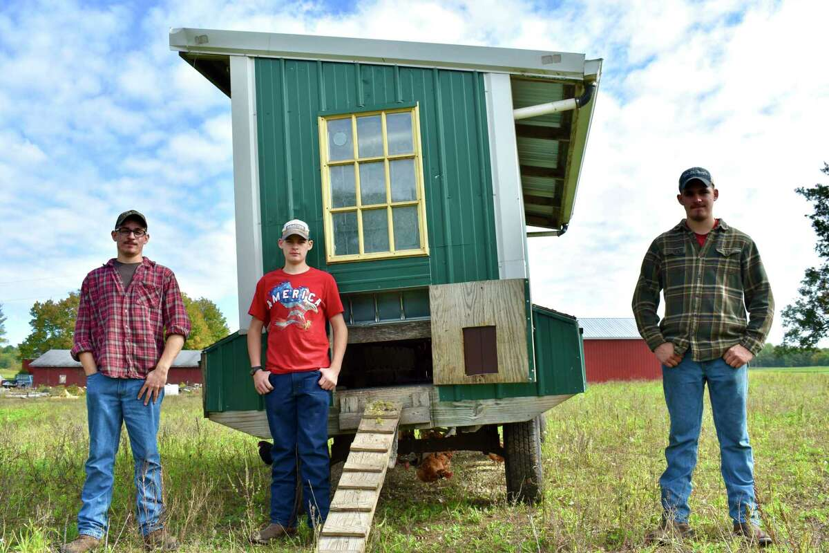 Brothers Sawyer, Scott and Jarrad Stilson help with work on their family farm which often includes upkeep of the farm's movable chicken coop. (Pioneer photo/Olivia Fellows)