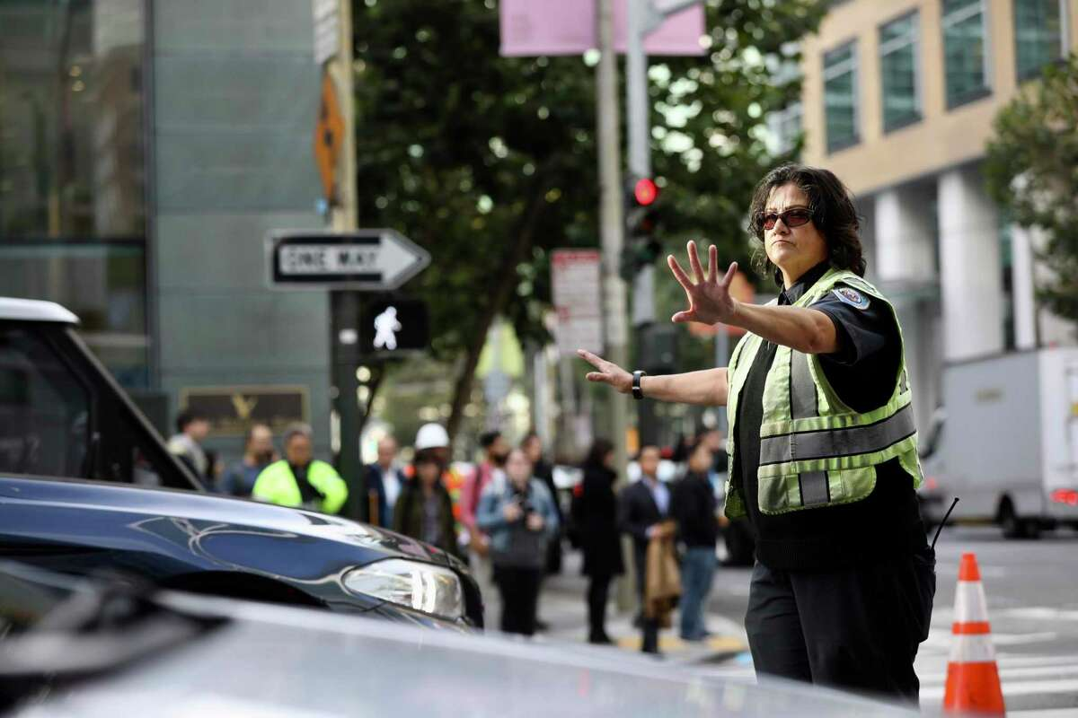 A traffic enforcement officer directs cars at Fremont and Howard near the Transbay transit center in 2018. A string of popular events will converge in downtown San Francisco this weekend, with Giants playoff games drawing crowds to Oracle Park as fans of the Blue Angels air show pack Crissy Field and Pier 39.