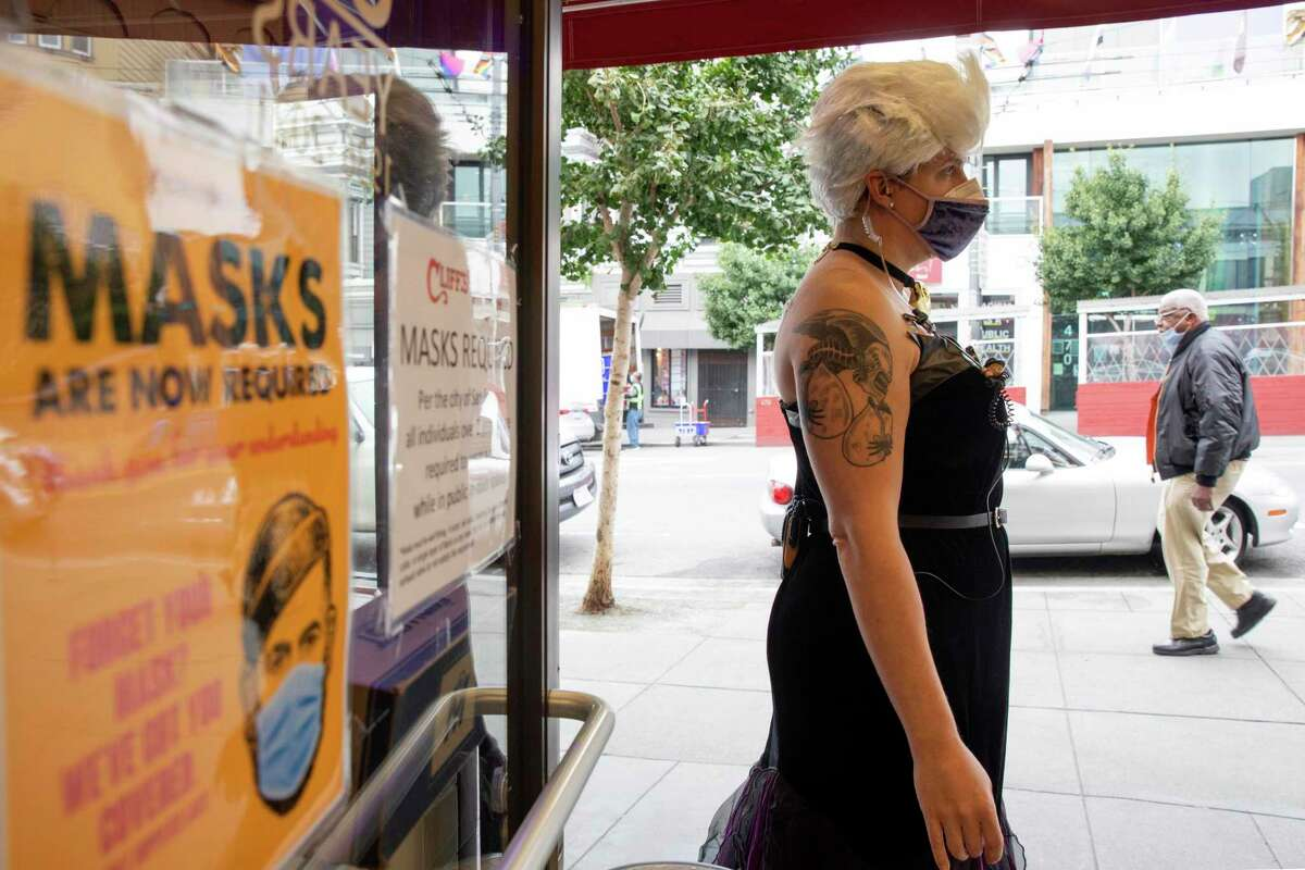 Piper Lind wears a mask and decorated costume while welcoming masked customers to Cliff's Variety on Castro Street in San Francisco, Calif. Wednesday, October 6, 2021.